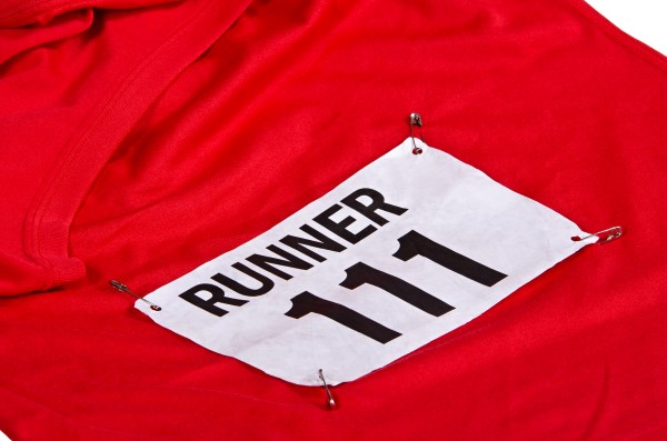 Race number on bib attached to the front of red running shirt